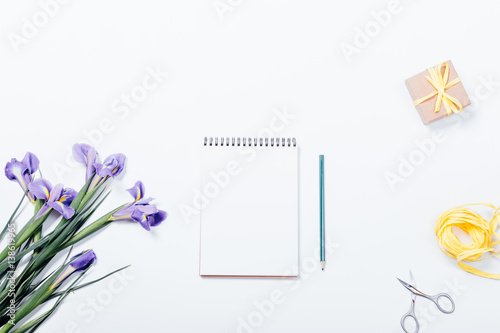 Poster Iris View from the top of a bouquet of irises, a notebook with a pencil, gift box, scissors and ribbon