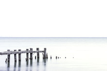 Posts Of Broken Pier Standing In A Light Blue Lake, White Sky Background, Room For Text