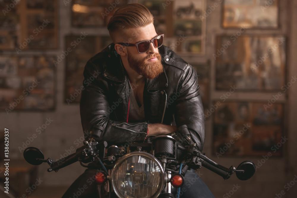 Fototapeta Guy in motorbike repair shop