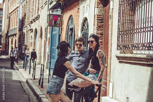 Fotografia  Trois jeunes personnes discutent dans la rue, paysage urbain