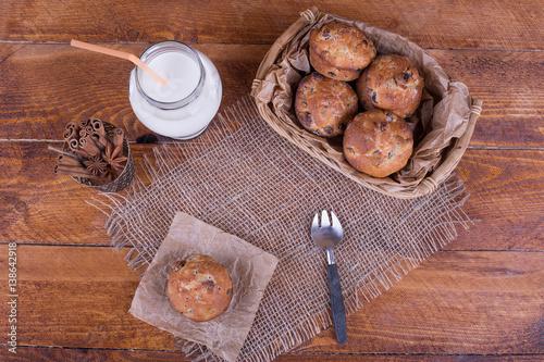 Fotobehang Koekjes muffins with raisins and milk on the newspaper