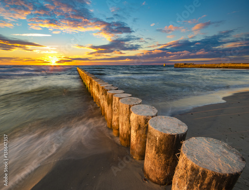 Papiers peints Gris Baltic sea at beautiful sunrise,wooden breakwater in the light of the setting sun