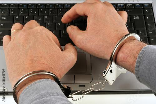 Fototapeta Homme menotté tapant sur le clavier d'un ordinateur
