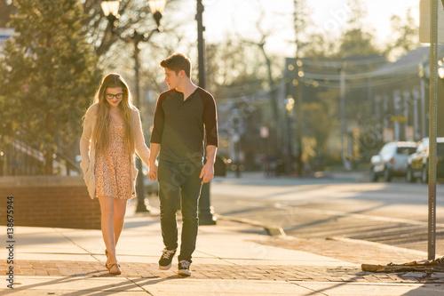 Fotografia, Obraz  Young couple walking down the sidewalk holding hands