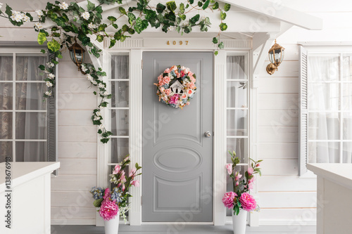 White small wooden house with gray door. spring flower decoration