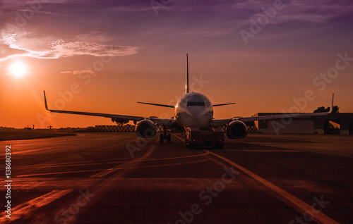 Fotografia  Commercial passenger jet in an airport at the sunset.