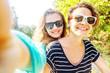 Two happy girlfriends making selfie outdoors