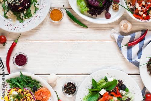 Fresh vegetable salads frame flat lay. Top view on white wooden table with free space for text between side dish buffet. Vegetarian cuisine, menu concept