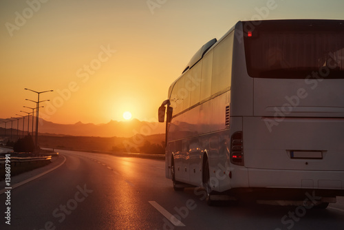 White bus driving on road towards the setting sun Wallpaper Mural