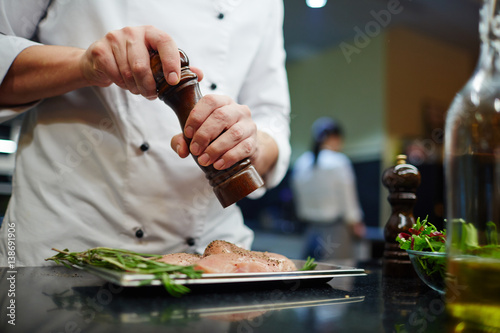 Fototapeta Man in uniform of chef seasoning lean meat with spices obraz