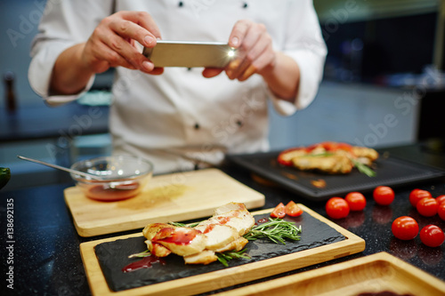 Photo  Chef photographing roasted chicken steak dressed by tomato sauce
