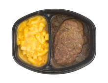 Top View Of A Salisbury Steak Meal With Macaroni And Cheese TV Dinner Isolated On A White Background.