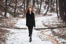 Striking Girl With Long Red Hair In Black Clothes. A Woman In A Black Coat Posing On A Background Of Winter, Autumn Nature. Female Street Fashion Style. Beautiful Elegant Redhead Model.