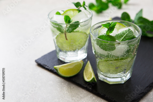Valokuva  Cold refreshing summer lemonade mojito in a glass on a slate board and stone background