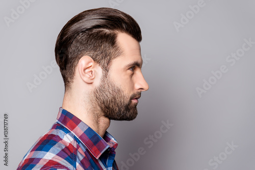 Valokuva  A profile portrait of a young handsome man with trendy stylish hairdo against gr