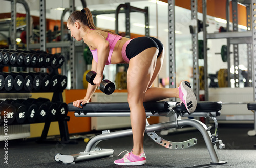 Spoed Foto op Canvas Fitness Beautiful sportive woman training with dumbbell in gym