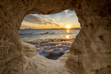 Fototapeta sunset over the sea seen from a cave