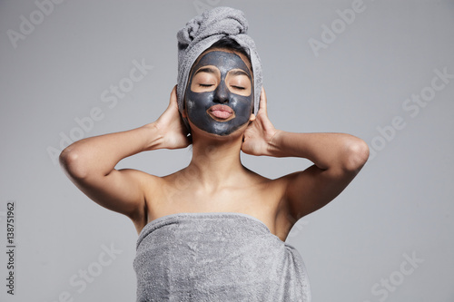 Fotografía  mixed race woman with clay coal grey facial cleansing mask treatment