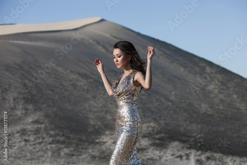 Plagát  Beautiful fashion asian model in a luxury golden dress posing in a desert