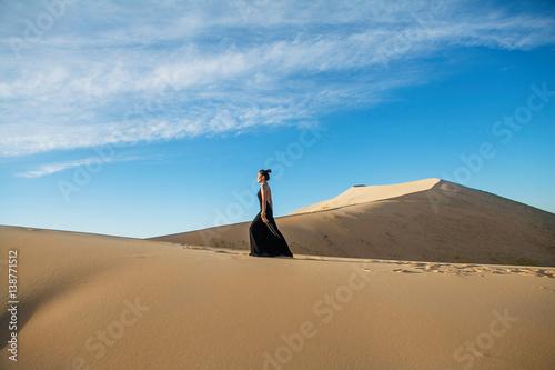 Photo  Fashion asian woman model posing in a black long dress in desert