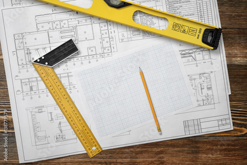 Valokuva  Wooden table with blueprints, a ruler with angle bar, a builders level, a pencil and cross section paper lying on it