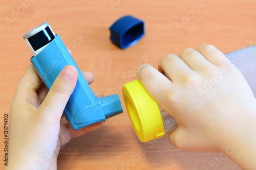 Small child holding asthma inhaler and spacer in his hands Canvas Print