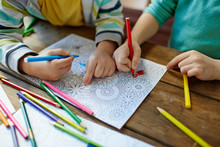 Close-up Shot Of Two Pairs Of Little Hands Coloring Mandala With Felt-tip Pens, Pencils Of Different Colors And Illustrations Laid On Wooden Table