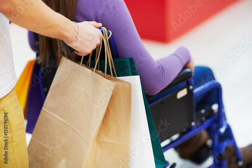 Fototapety, obrazy: Extreme close-up view of woman in wheelchair being pushed by assistant with paper bags while shopping in mall
