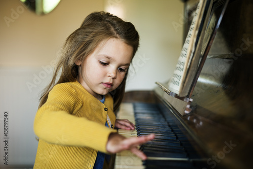 Fotografie, Obraz  Adorable Cute Girl Playing Piano Concept