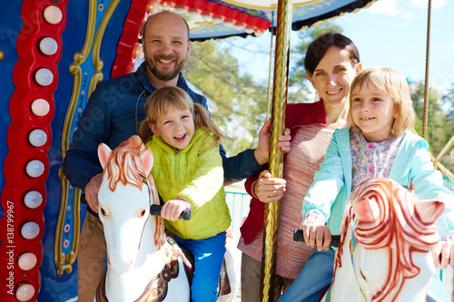 Poster Amusementspark Pretty little girl in green windbreaker and her elder sister riding on carousel while their cheerful parents standing behind them and posing for photography