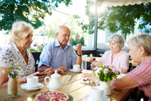 Senior Friends Gathered Together In Summer Cafe In Order To Drink Tea With Pastry And Playing Dominoes