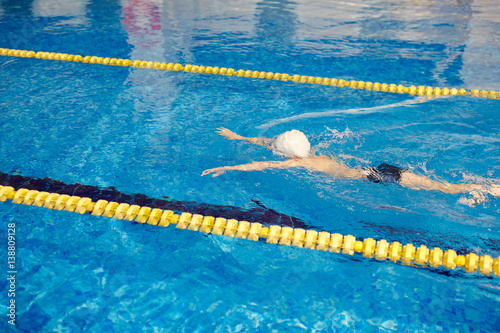 High angle of unrecognizable school age boy swimming fast ...