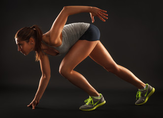 Young female athlete standing in race start position.Studio shot on dark background.