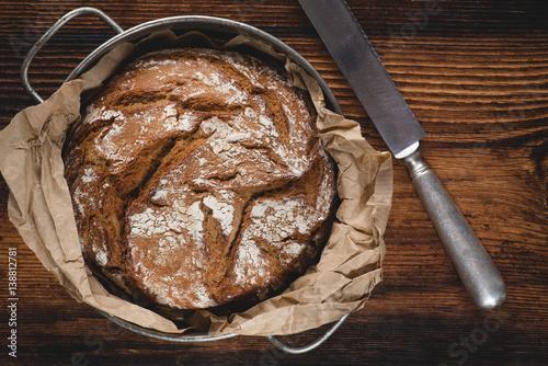 swiezy-bochenek-chleba-z-nozem-do-masla-na-drewnianym-stole
