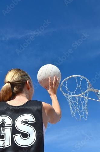Fotografiet  Blond caucasian woman shoots a netball into a netball ring