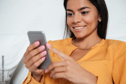 Fotografía  Happy businesswoman with smartphone lying in bed