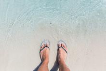 Male Feet Wearing Female Flip Flops At Beach