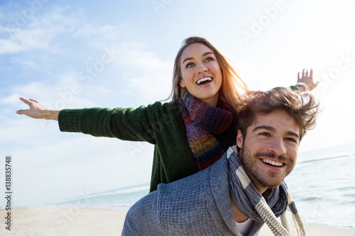 Fototapeta Happy young couple enjoying the day in a cold winter on the beach. obraz