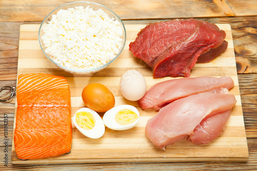 Fotografia  Protein diet, fish, cheese, eggs, meat and chicken on a wooden background