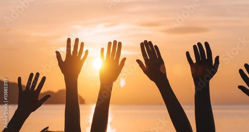 Many hands raised against sunset sky