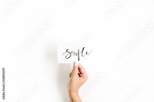 Fotografie, Obraz  Minimal pale composition with girl's hand holding card with word Simple written in calligraphic style on paper on white background