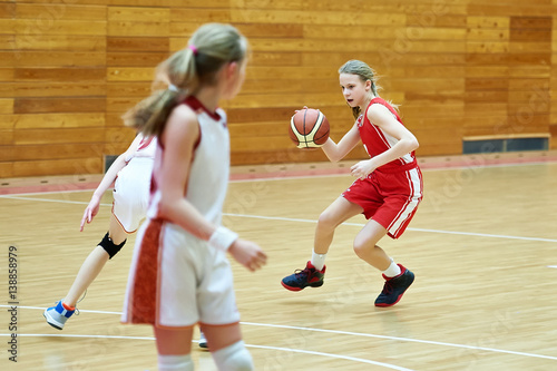 Girls in sport uniform playing basketball indoors