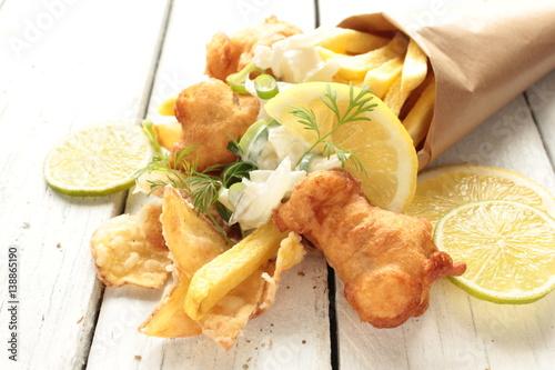 Fotografie, Obraz  Backfisch Pommes Kartoffelchips Fish and Chips Tüte Tisch