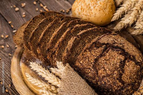 kromki-ciemnego-chleba-z-klosami-pszenicy-na-drewnianym-stole