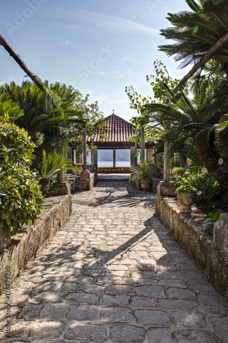 Lush vegetation, paved passageway and a pavilion at the arboretum in Trsteno, Croatia. Wall mural