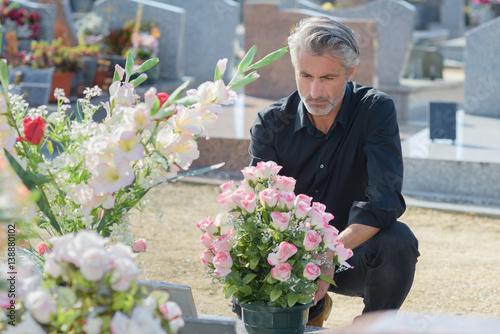 Foto op Canvas Begraafplaats Man in black knelt at grave