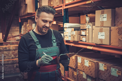 Storekeeper with manual pick list on a warehouse Fototapete