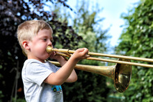 Profile Of The Small Boy Trying To Play Trombone