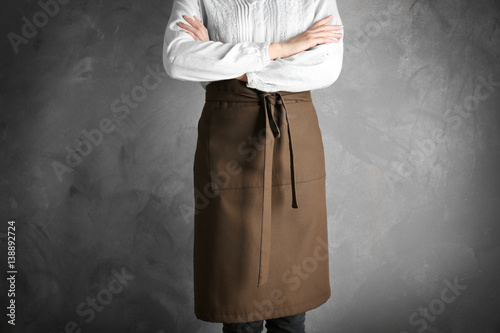 Cuadros en Lienzo Woman wearing apron on color background