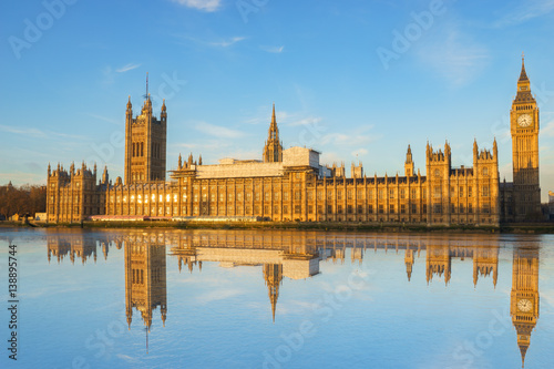 Fotomural Big Ben and Westminster parliament with blue sky and water reflection in London,